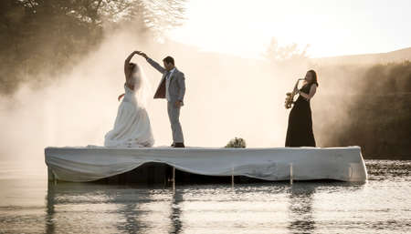 Bride and Groom dancing on a lake to music. Standard-Bild
