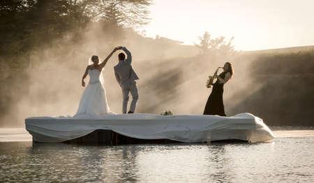 Braut und Bräutigam tanzen auf einem See zu Musik. Standard-Bild - 79148421