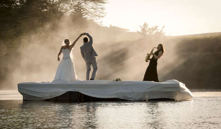 Bride and Groom dancing on a lake to music. Zdjęcie Seryjne