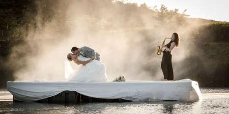 Braut und Bräutigam tanzen auf einem See zu Musik. Standard-Bild - 79148420