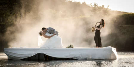 Bride and Groom dancing on a lake to music. 版權商用圖片
