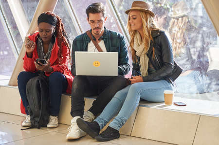 3 young adults entrepreneurs or students group mixed race around laptop having a discussion Stock Photo