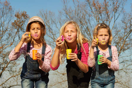 Three girls kids sisters blowing bubbles with soap in a farm field