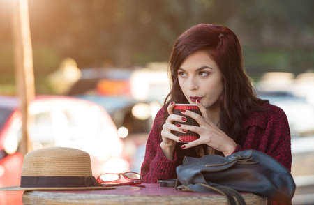 Young woman enjoying a beverage at an outdoor cafe