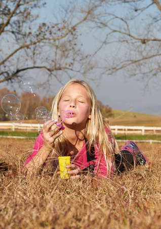 Young girl child kid blowing soap bubble in a field