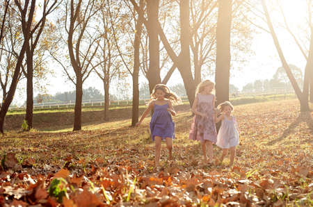 Young girls children kids playing running in fallen autumn leaves