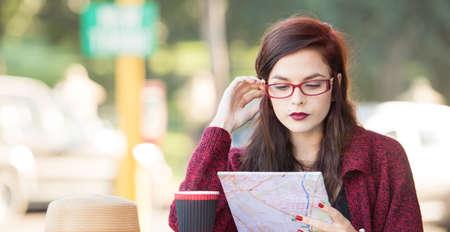 Young beautiful traveler looking at a map.