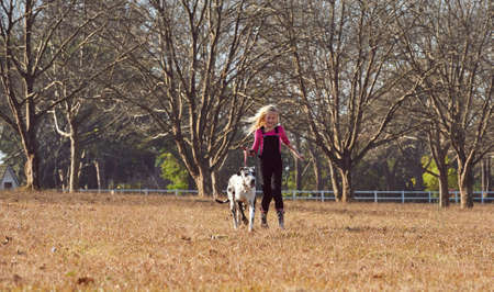 Young teen girl and her dog running playing in open field Zdjęcie Seryjne