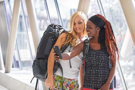 2 female travellers in airport hallway taking selfies Zdjęcie Seryjne
