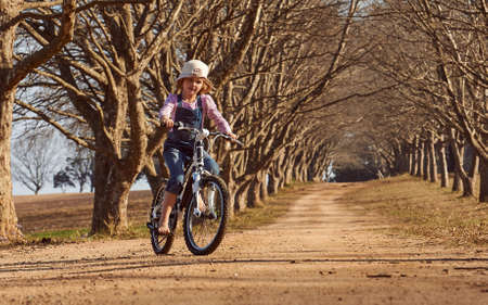 Young girl riding her bicycle bike down dirt road tree lined avenue