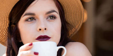 close up of young attractive woman sitting at cafe drinking coffee