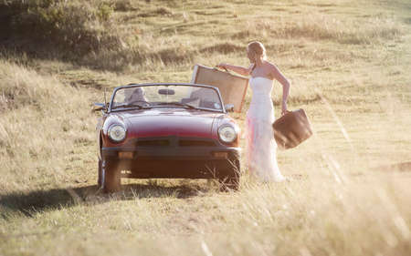 Woman packing suitcases in a vintage sports car driving off with man. Standard-Bild