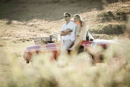 Couple drinking wine in a grass field on a vintage sports car.