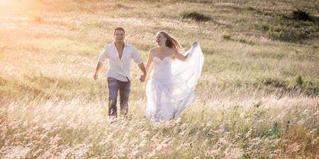 Couple walking together holding hands in an open field. Standard-Bild