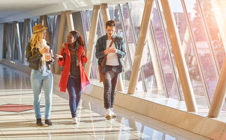 3 young adults entrepreneurs or students group mixed race walking with coffee and cellphone Zdjęcie Seryjne