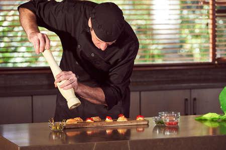 Restaurant hotel private chef seasoning food in kitchen Zdjęcie Seryjne