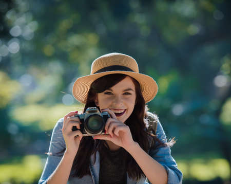 surrounds: Young happy traveler exploring surrounds with film camera