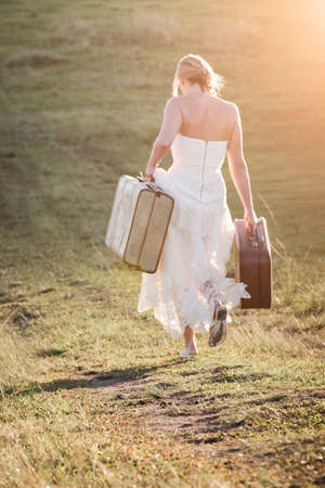 Woman walking carrying suitcases in white dress.