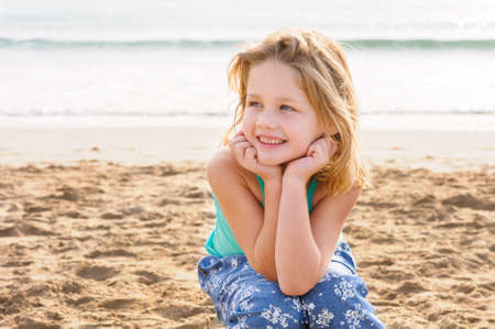 looking into camera: Young girl sitting on ball on beach looking into camera with sea in background Stock Photo