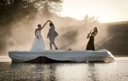 Braut und Bräutigam tanzen auf einem See zu Musik. Standard-Bild - 79148432