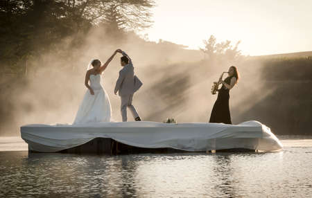 Bride and Groom dancing on a lake to music. Stock Photo