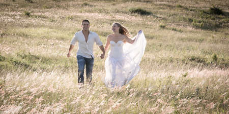 Paar zu Fuß zusammen Händchen haltend in einem offenen Feld. Standard-Bild - 79148433
