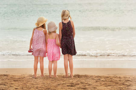 beachfront: 3 sisters stand on beachfront facing the ocean.