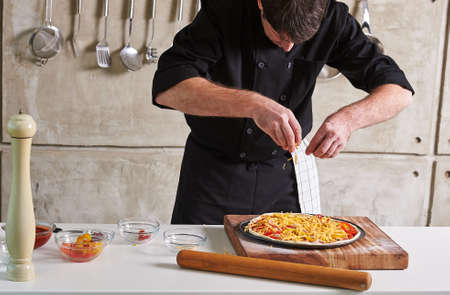 toppings: Restaurant hotel private chef preparing a pizza with toppings Stock Photo