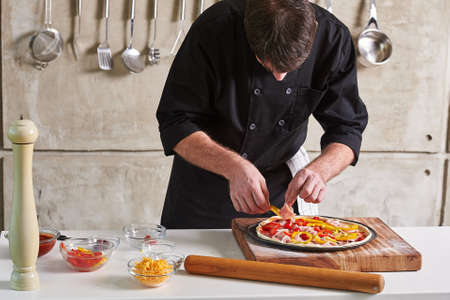 Restaurant hotel private chef preparing a pizza with toppings Zdjęcie Seryjne