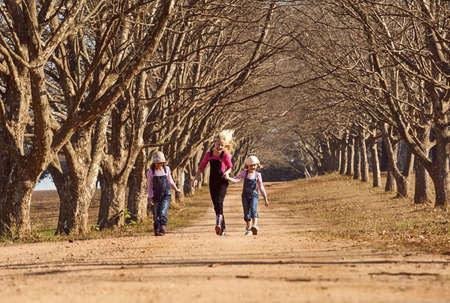 Drei Mädchen Schwestern Laufen Skipping unten Feldweg von Bäumen gesäumten Allee Standard-Bild - 79148434
