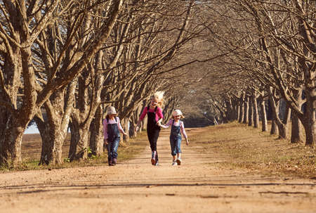 Three girls sisters running skipping down dirt road tree lined avenue