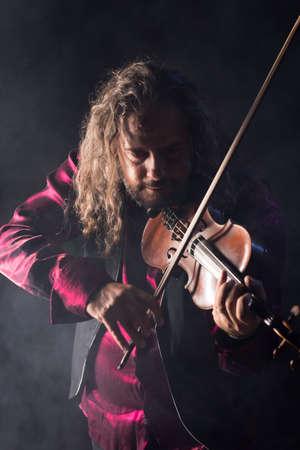 handsome man playing classical violin through blue smoke Standard-Bild