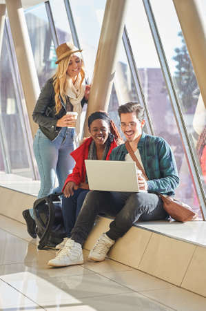 young entrepreneurs: 3 young adults entrepreneurs or students group mixed race around laptop having a discussion Stock Photo