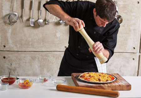 Restaurant hotel private chef seasoning a pizza in the kitchen