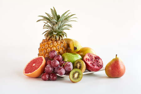 mixed fruit: healthy platter of whole mixed fruit on white background