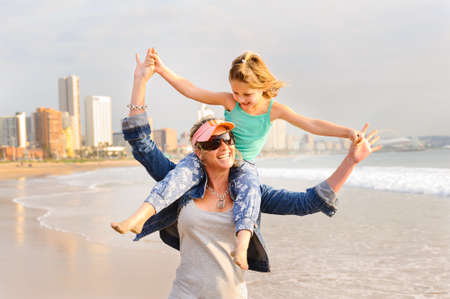 beachfront: Young girl sitting on moms shoulder while walking on beachfront Stock Photo