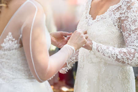 Same sex gay lesbian bride places ring on finger during wedding ceremony