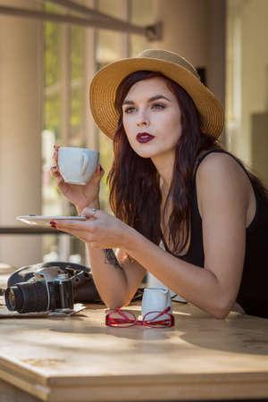 young beautiful traveler enjoying a coffee at street cafe