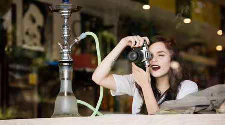 Young woman sitting at shop window taking photos and having fun