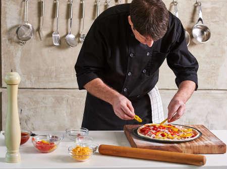 Hôtel restaurant chef privé assaisonnement une pizza dans la cuisine Banque d'images - 65266048