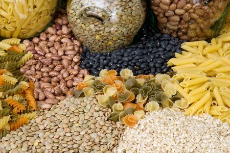 lentils: Raw pasta, beans, lentils and rice as a background pattern with glass jars Stock Photo