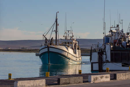 Blue and white, wooden trawler returning from sea,coming into harbour, after fishing for anchovy and pichards