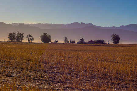 silhoutted: Farmland in early morning glow, silhoutted, mountains in distance Stock Photo