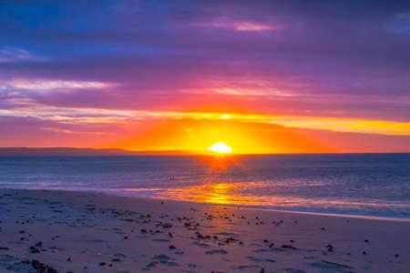 africa sunset: Rosso tramonto sul mare, spiaggia di sabbia illuminata dal sole, tanti colori Archivio Fotografico