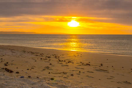 Yellow sunset over beach, sand lit by sun Stock Photo