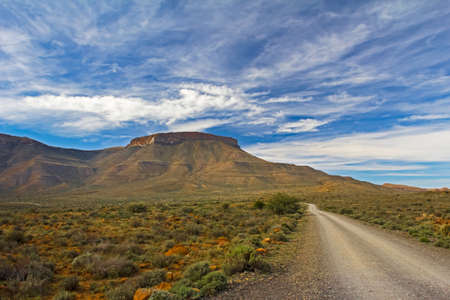 Karoo flat-topped mountain with dirt road blue sky and white clouds