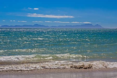 View across blue-green choppy waters in False Bay towards Table Mountain Stock Photo