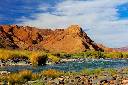 Reddish Mountains River and Blue Sky