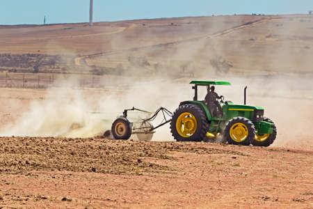 Green tractor ploughing dusty field 写真素材