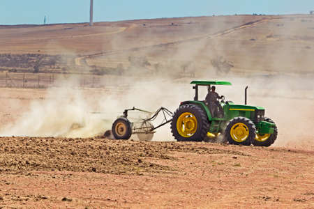 Green tractor ploughing dusty field Stockfoto